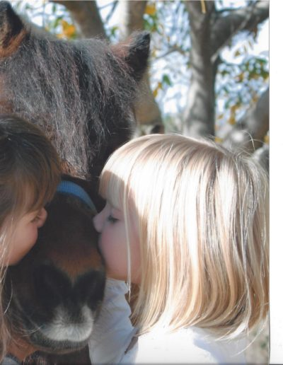 Two little girls kissing a ponies nose